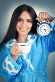 Young Woman in Bathrobe Holding an Alarm Clock and a Cup of Coffee — Stock Photo