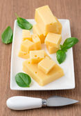 Cheese and basil leaves on cutting board — Stock Photo