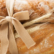 Bunch of fresh bread and wheat ears close up — Stock Photo #27045649