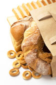 Fresh bread in paper bag on the white — Stock Photo