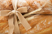 Bunch of fresh bread and wheat ears close up — Stock Photo