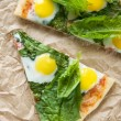 Two pieces of pizza with quail eggs and spinach — Stock Photo
