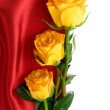 Yellow roses on the red satin with space for text — Stock Photo