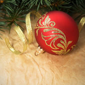Xmas ornaments and spruce on crumpled paper background — Stock Photo