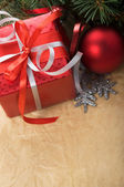 Xmas gift box and ornaments on old paper background — Stock Photo