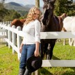 Cowgirl and black beauty — Stock Photo