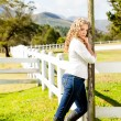 Stock Photo: Cowgirl at picket fence
