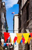 Colorful flags in narrow streets — Stock Photo