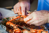 King prawns and oily fingers — Stock Photo
