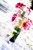 Bubbly and candles among crystal — Stock Photo