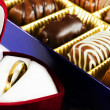 Pralines and wedding ring - Stock Photo