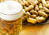 Glass of beer with peanuts. — Stock Photo