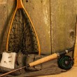 Stock Photo: Fly fishing gear on burlap against ceader wood wall