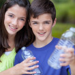 Boy and girl holding clear bottle for recycling - Stock Photo