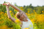 Woman stretching in ragweed flowers — Stock Photo