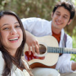 Young man playing guitar for woman — Stock Photo