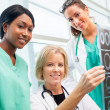 Stock Photo: Female doctor and nurses look at CT scan