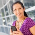 Hispanic woman holding cell phone — Stock Photo #25952883