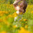 Royalty-Free Stock Photo: Woman practicing yoga in meadow of yellow flowers