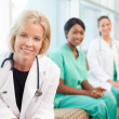 Smiling female doctor sitting with smiling female nurses — Stock Photo #25954993