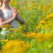 Woman meditating in meadow of yellow flowers — Stock Photo #25955691