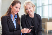 Businesswomen with cell phone in lobby — Stock Photo