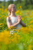 Woman meditating in meadow of yellow flowers — Stock Photo