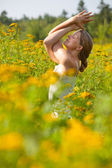 Woman practicing yoga in meadow of yellow flowers — Stock Photo