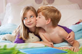 Brother kissing sister on cheek. — Stock Photo