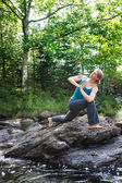 Woman practicing yoga on rocks beside stream — Stock Photo