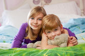 Siblings lying on bed toegther. — Stock Photo