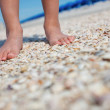 Boys feet on seashells — Stock Photo