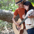 Young man playing guitar for woman in trees — Stock Photo