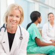 Stock Photo: Smiling female doctor sitting with female nurses