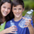 Boy and girl holding clear bottle for recycling — Stock Photo