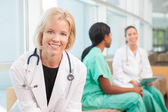 Smiling female doctor sitting with female nurses — Stock Photo