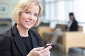 Businesswoman holding cell phone — Stock Photo