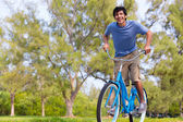Young Man on bike wth trees — Stock Photo