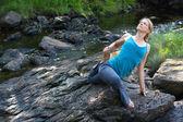 Woman practicing yoga on rocks beside stream — Stock Photo