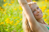 Woman arms stretched high in meadow of yellow flowers — Stock Photo