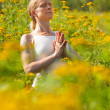 Woman meditating in meadow of yellow flowers — Stock Photo #25980591