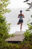 Woman doing yoga on dock by lake — Stock Photo