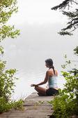 Woman meditating on dock by lake — Stock Photo