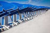 Hilera de sillas azules y paraguas — Foto de Stock