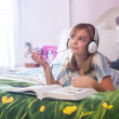 Teenaged girl on bed with headphones. — Stock Photo