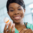 Stock Photo: Nurse examines prescription bottle