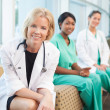 Smiling female doctor sitting with smiling female nurses — Stock Photo