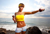 The girl with a sports figure does exercises with dumbbells — Stock Photo