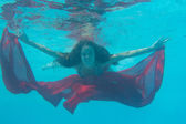 Woman submerged with red fabric under water — Stock Photo