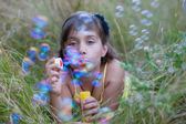 Little girl having fun with soap bubbles — Stock Photo
